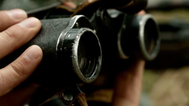 Soldier his equipment looking through binoculars video