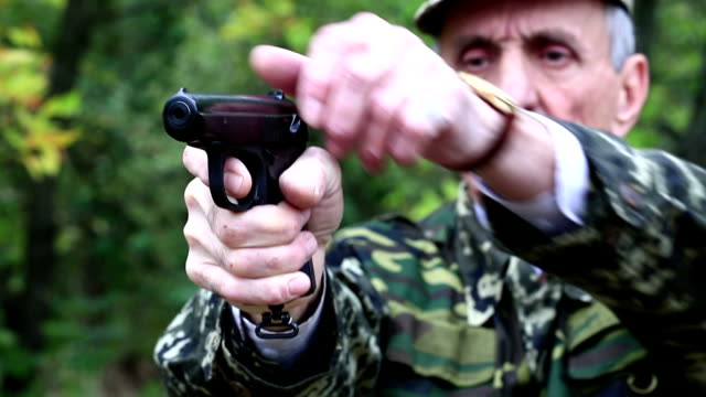 Soldier in military uniform shoots a revolver video