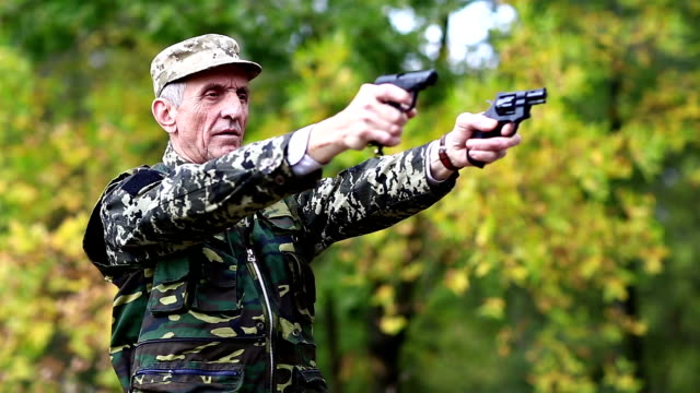 Soldier in military uniform shoots from two pneumatic handguns video