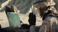Soldier is Using Laptop Computer for Tracking the Target and Radio for Communication During Military Operation in the Desert video