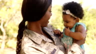Soldier mother holding her daughter in a park video