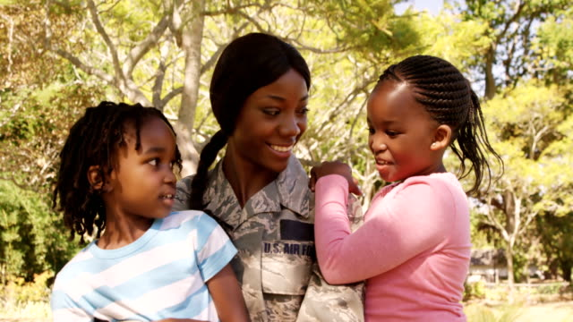 Soldier mother holding her two children in a park video