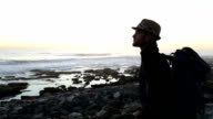 Solo Traveler on rocky coastline at sunset video