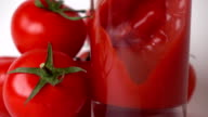 Some red tomatoes and tomato juice being poured into glass. Super slow motion video