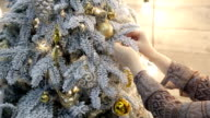 Somebody tie gold ribbon from organza as decoration to Christmas tree video