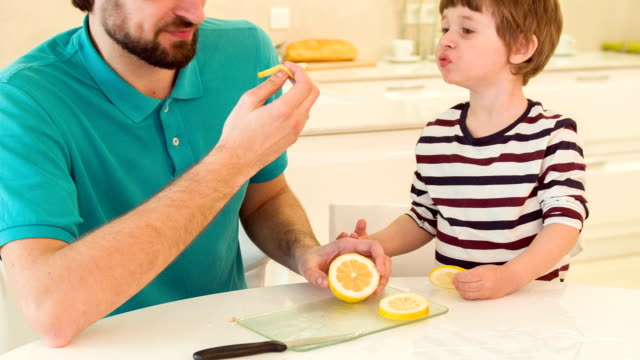 Son and dad eating lemon together video