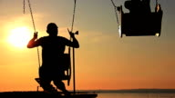 son and father swinging on a swing at sunset, dawn, near the river, silhouettes video
