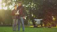 Son Controls Flying Drone while Father Watches. In the Park. video