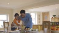 Son helping father to make pasta salad in kitchen video