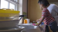 Son Helping Mother To Wash Dishes In Kitchen Sink video