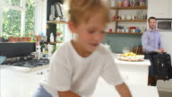 Son Playing In Kitchen Greeting Father Returning From Trip video