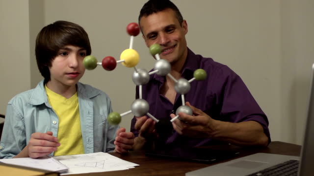 Son Shows Father his Science Project of a Molecule video