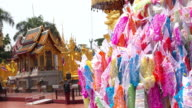 Songkran festival thailand, traditional flag decorated on sand heap at Wat para that Hariphunchai in Lamphun video