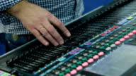 A Sound Engineer Using a Mixing Desk or Mixing Console to Mix a Track in a Recording Studio video