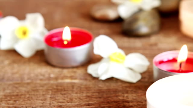 Spa still life containing bath salt, rocks, massage oil, candles and flowers video