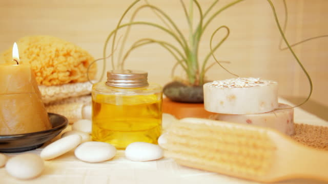 Spa still life of candle, massage oil and pebbles video