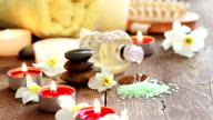 Spa still life of massage oil, towel, rocks and flowers video