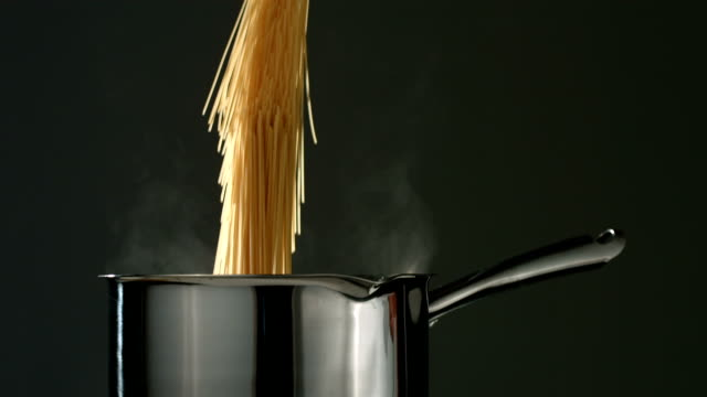 Spaghetti is dropped into boiling water, slow motion video