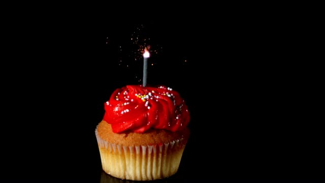 Sparkler burning on red birthday cupcake video