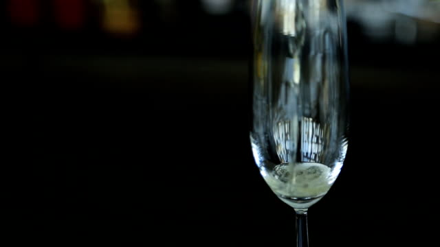 Sparkling champagne is filling crystal wine glass that stands on table video