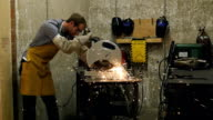 Sparks fly as Caucasian man in metal workshop cuts piece of metal with electric saw video
