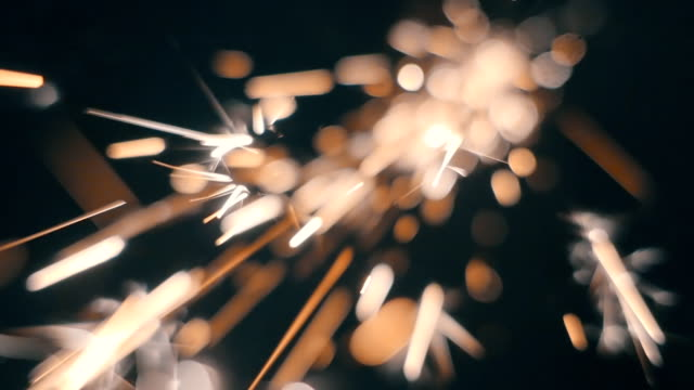Sparks fly directly into the camera against a black background. Slow mo, slo mo video