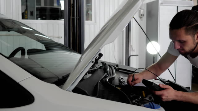specialist mechanician man stands near open hood checks wiring automobile system, Engine review, fault diagnosis video