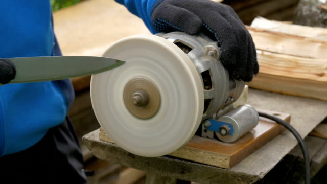 A specialist sharpens a table knife. video