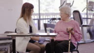 Speech therapist working with a geriatric patient in a clinic video
