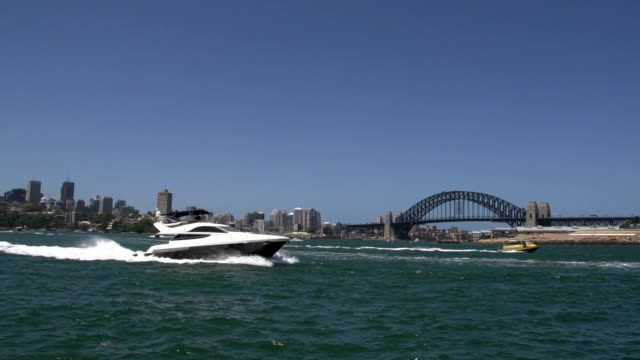 Speedboat and small water taxi passing by in front of the harbour bridge video
