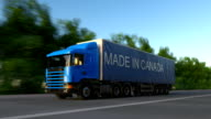 Speeding freight semi truck with MADE IN CANADA caption on the trailer. Road cargo transportation. Seamless loop FullHD clip video