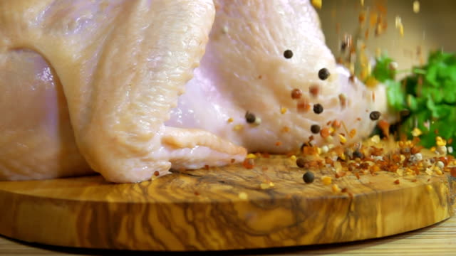 Spices are falling on a wooden board with raw chicken video