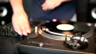 DJ spinning turntables in club video