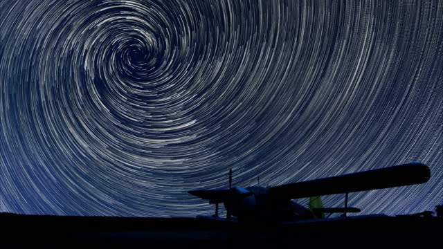 Spiral Star trails over small airport lonely airplane video