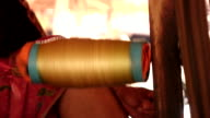 Spools pull silk threads from silk cocoons video