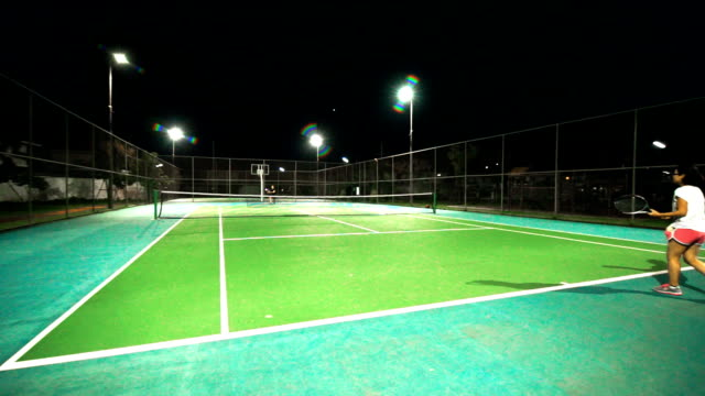 Sport & Family : A woman playing tennis on a tennis court at night, view from back. video