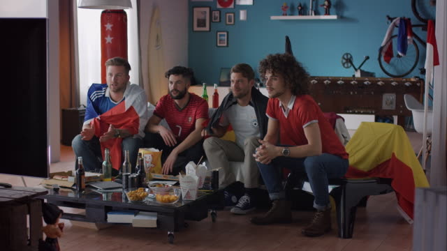 Sport fans sitting on couch watching tv disappointed video
