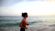 Sport leisure girl running on the beach of Mediterranean Sea at sunset video