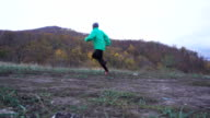 Sport Man jogging cross country running. . Fit male runner exercise training and jumping outdoors in mountain nature. Slow Motion. video