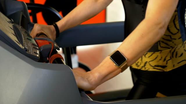 Sportive woman wearing smartwatch doing sport activity on treadmill video