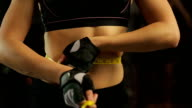 Sportive woman with flat tummy measuring her waist, controls weight video