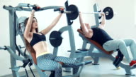 Sports couple doing inclined bench press and drink water video