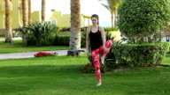 Sports girl doing basic exercises from yoga standing barefoot on the lawn. Brunette in stylish sports clothes does gymnastics on a background of swinging palms at the resort. video