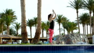 Sports girl doing basic exercises from yoga standing on the edge of the blue pool. Brunette in stylish sports clothes does gymnastics on a background of swinging palms at the resort. video