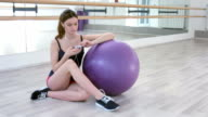 Sports girl listening music in dancing room video