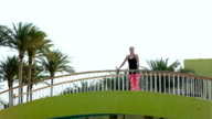 A sports girl stands on the footbridge looking around and enjoying the nature that surrounds her. The brunette stopped for a rest. video
