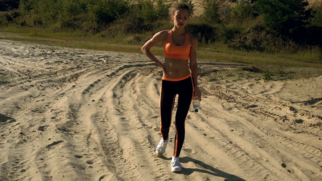 sports lady after workout walks with water in bottle in her hands video