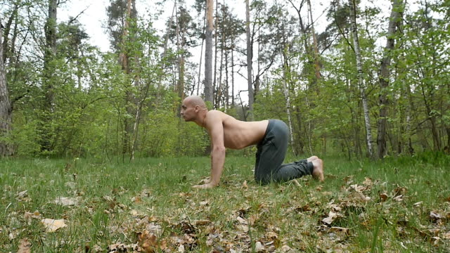 Sports man bend the back and meditating in the forest video