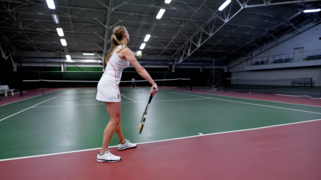 A sports woman in white clothes serves a ball feed through the grid while playing tennis in the gym, the sportswoman continues to beat the balls video