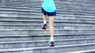 sports woman legs running up on stone stairs video